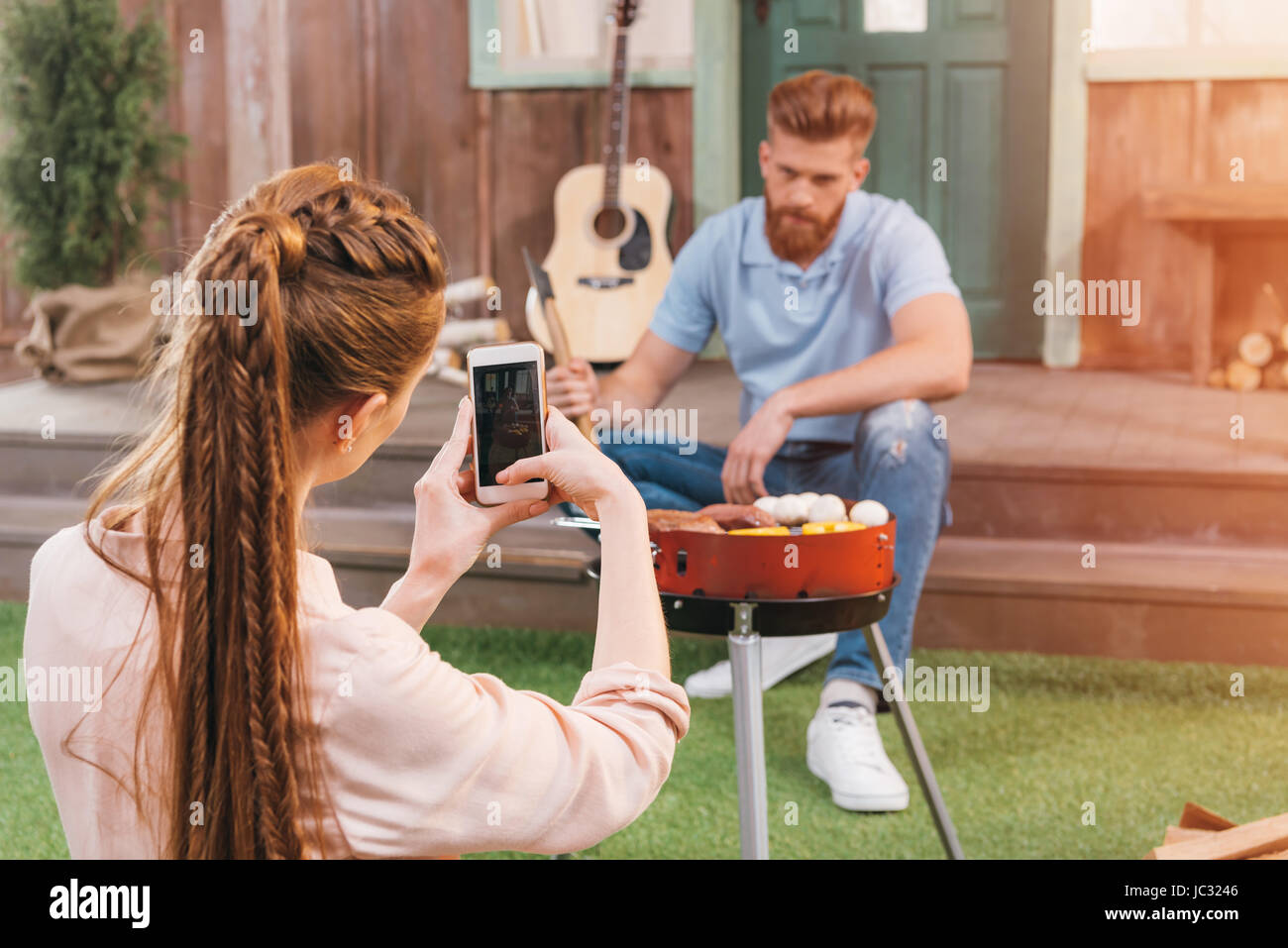 woman taking photo of man grilling meat on porch - Stock Image