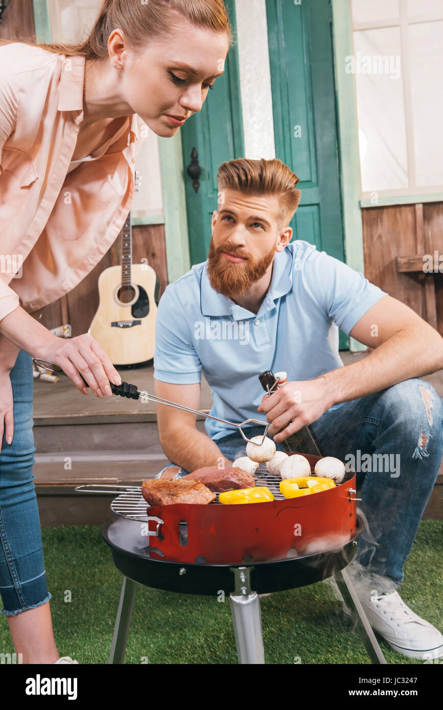 man and woman roasting meat and vegetables on barbecue grill - Stock Image
