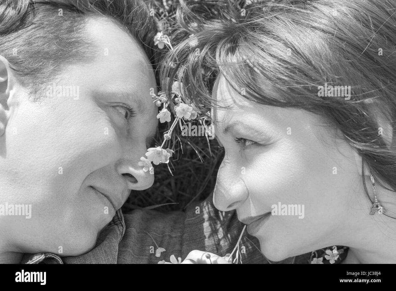 Affectionate young couple looking at each other in park. Love story. Black and white. - Stock Image