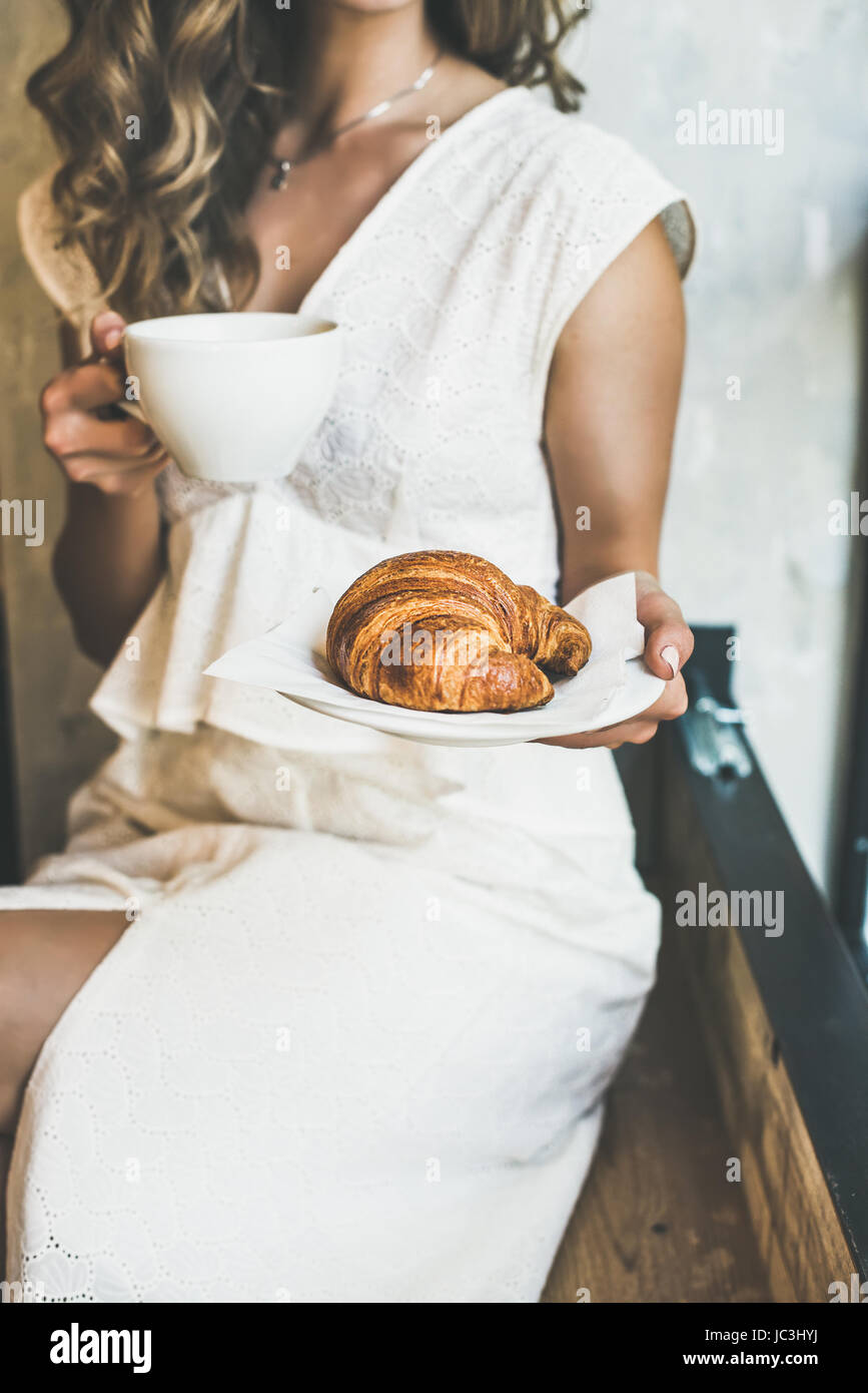 Blond woman holding fresh croissant and cup of cappuccino - Stock Image