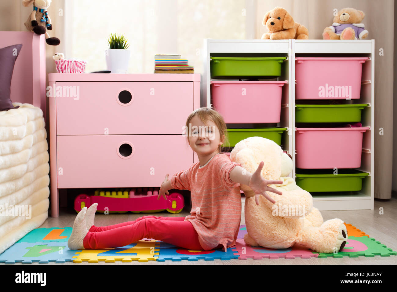 Cute little girl with a big teddy bear sitting on the floor in the children's room - Stock Image