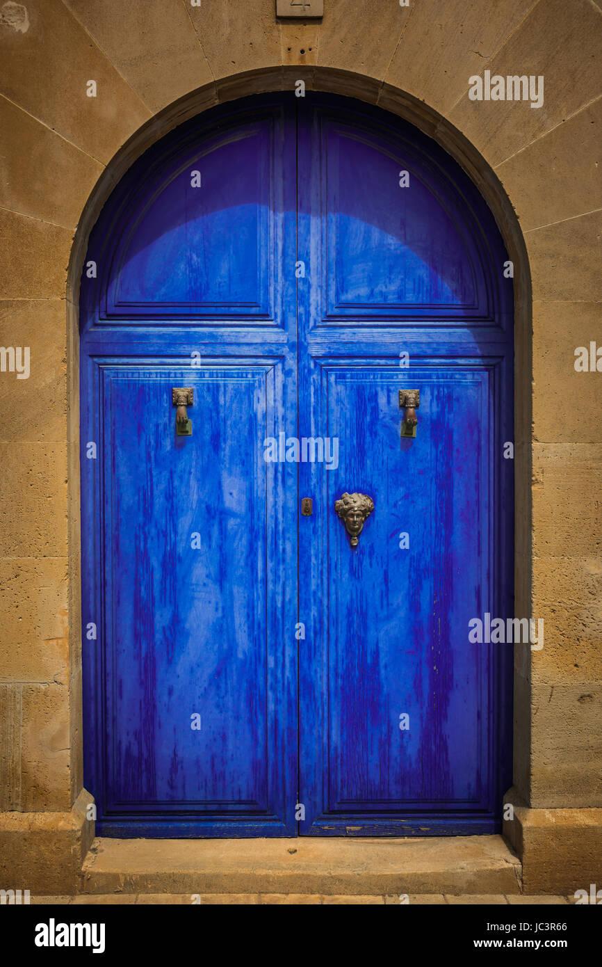 Weathered blue wooden door with golden knocker and handels - Stock Image