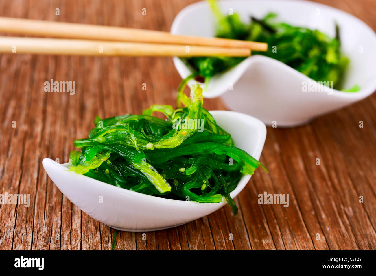goma wakame or seaweed salad in some white ceramic bowls, on a rustic wooden table - Stock Image