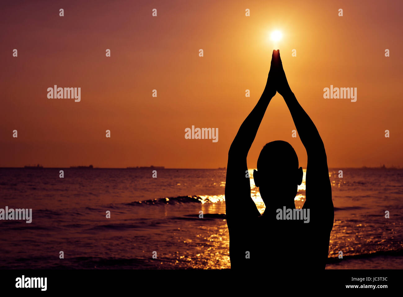the silhouette of a young caucasian man practicing yoga in front of the sea in backlight - Stock Image