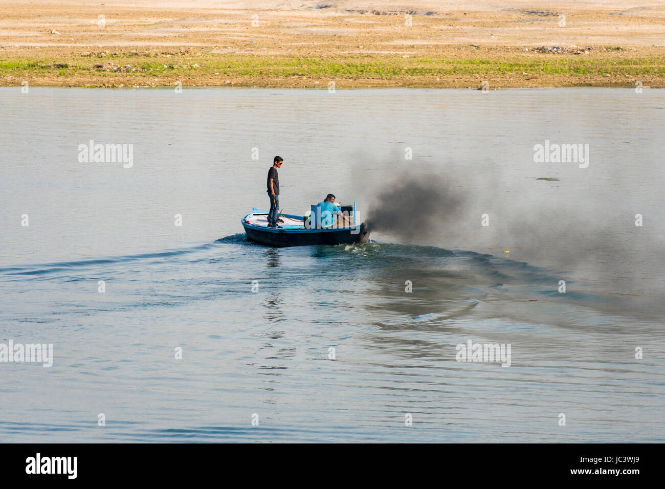 The engine of a motor boat is producing black exhaust gases on the holy river Ganges - Stock Image