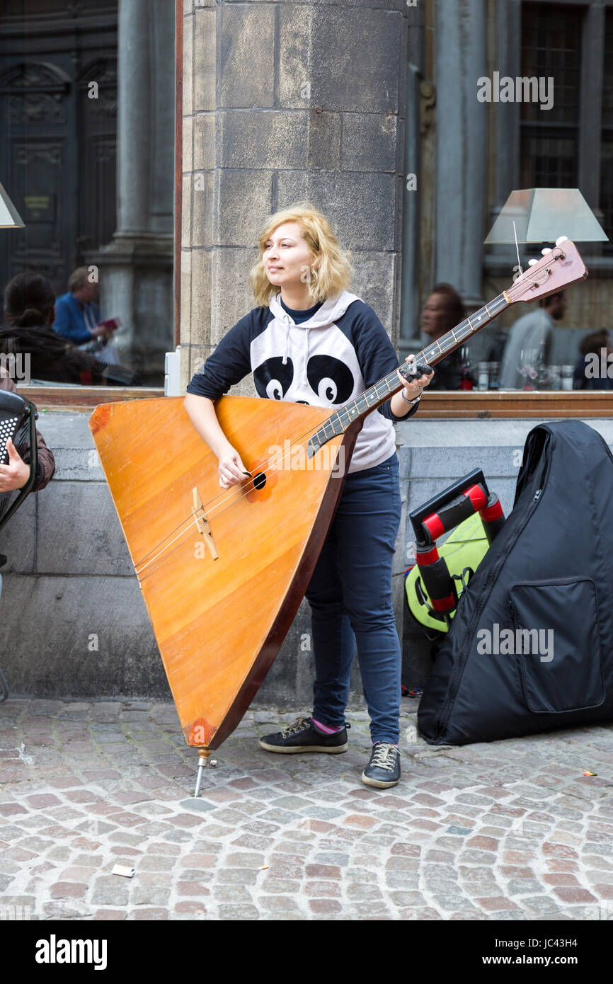 A street musician playing the Balalaika in Bruges, Belgium - Stock Image