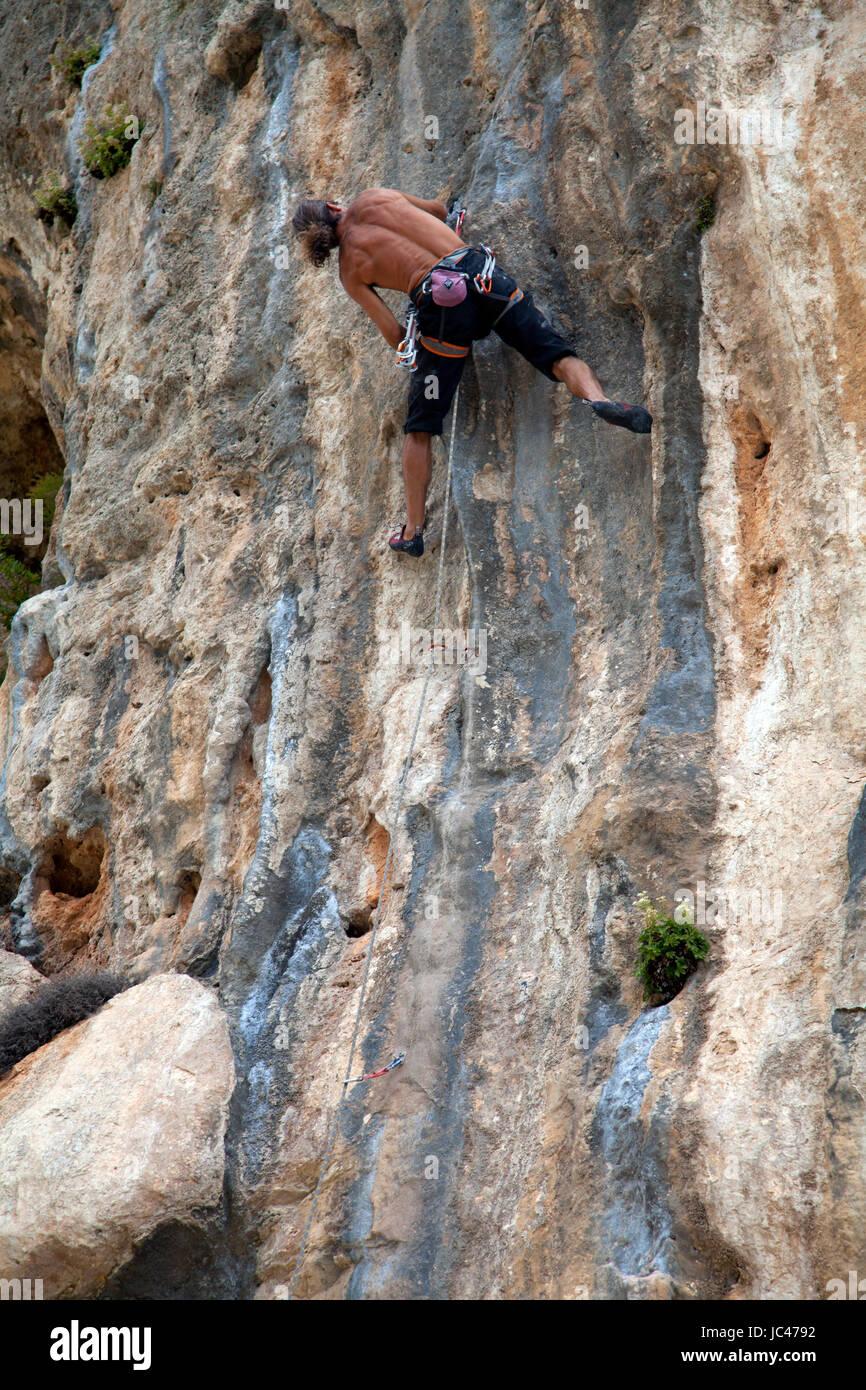 Mann klettert an einem Seil eine steile Felswand hinauf Stock Photo
