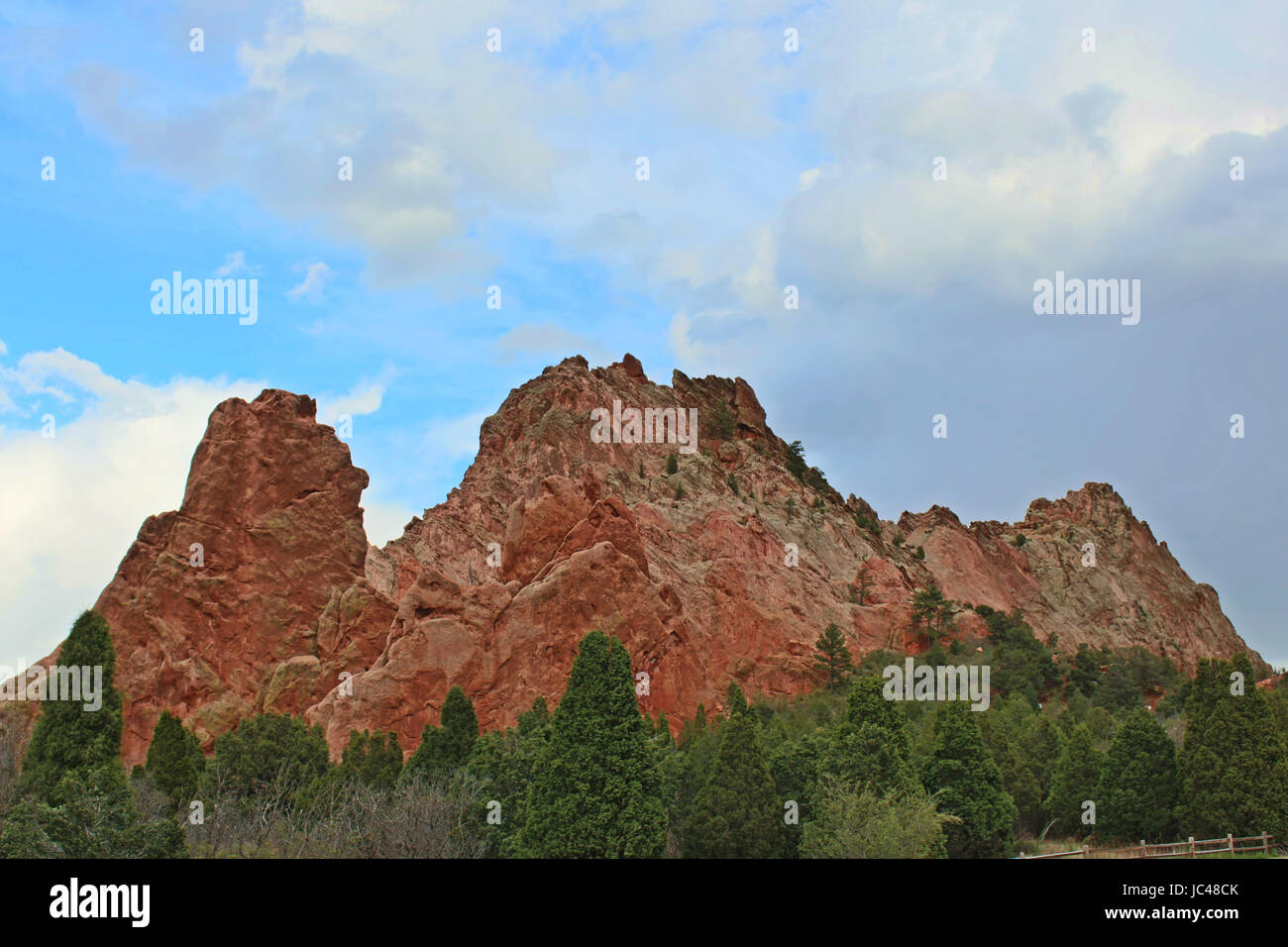 Large rock formation, made of red rock, and evergreentrees along a hiking trail at the Garden of the Gods in Colorado - Stock Image
