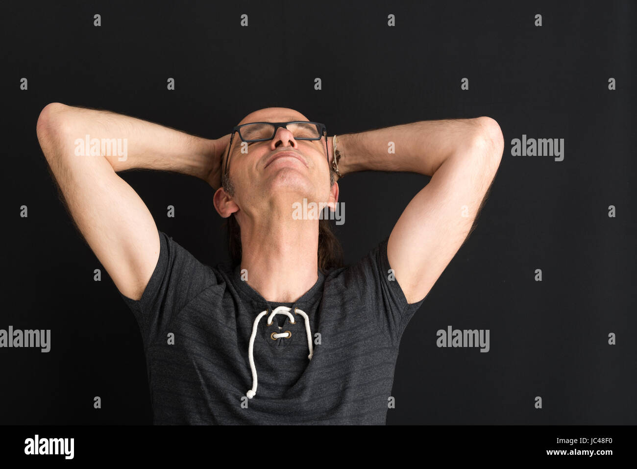 Portrait of a easygoing middleaged european adult - studioshot against dark background - Stock Image