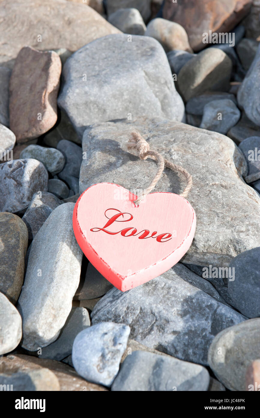single red wooden love heart on a pebble beach in Ireland - Stock Image