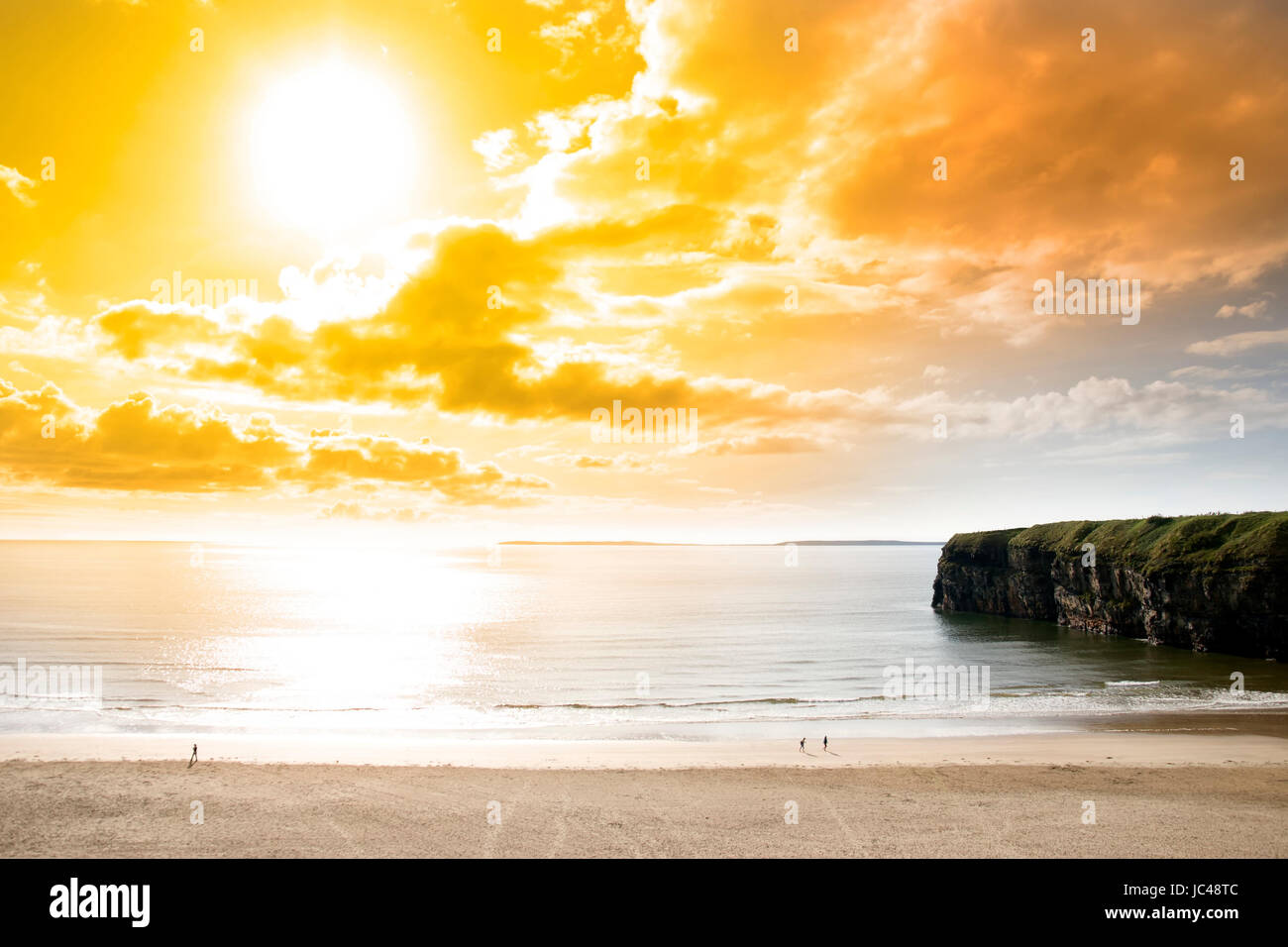 tourists walking the Ballybunion beach near cliffs in county Kerry Ireland on a beautiful summers day - Stock Image