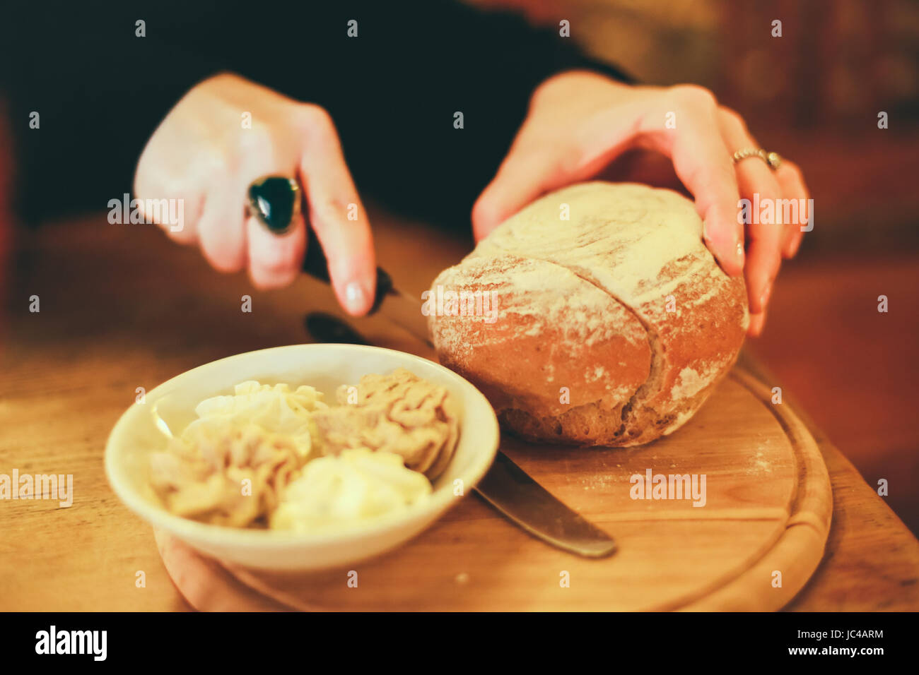 Close up shot of woman cutting home made bread on a wooden board, selection of butters and pate in a bowl next to - Stock Image