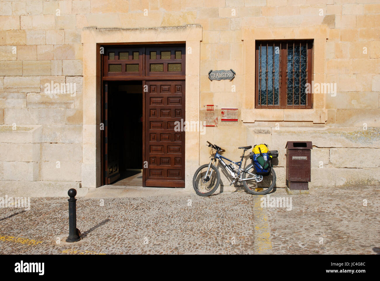 Entrance to monastery and pilgrim's bike. Santo Domingo de Silos, Burgos province, Castilla Leon, Spain. - Stock Image
