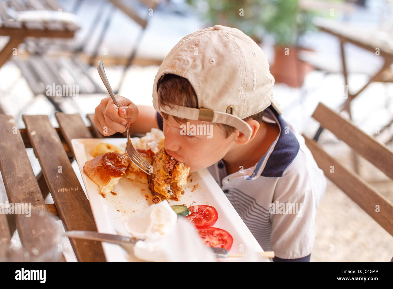 Little angry boy eating junk food in outdoor restaurant - Stock Image