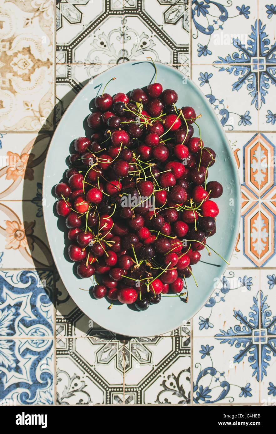 Fresh sweet cherries over oriental ceramic tiles background, top view - Stock Image