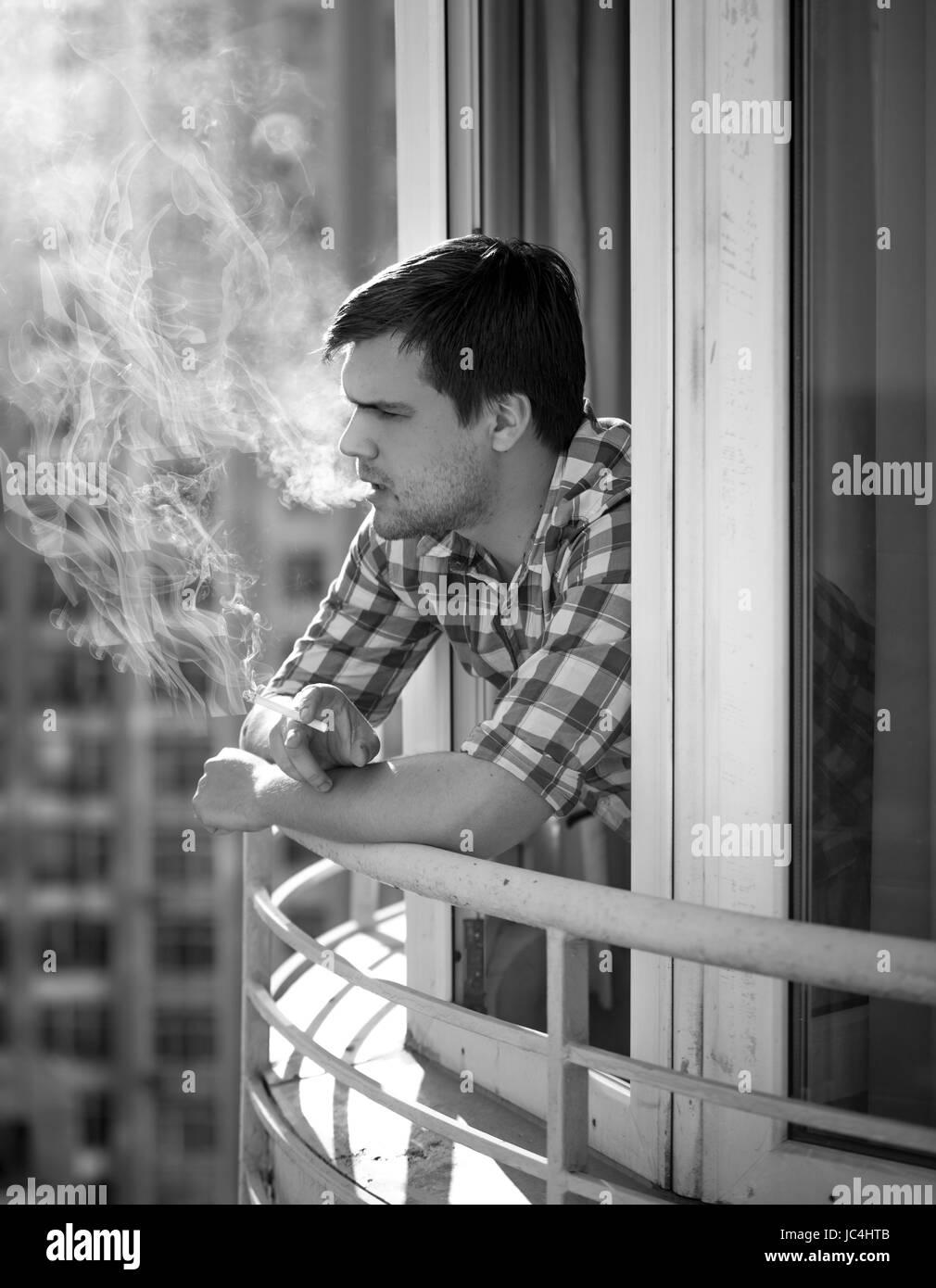 Monochrome portrait of depressed man smoking cigarette stock