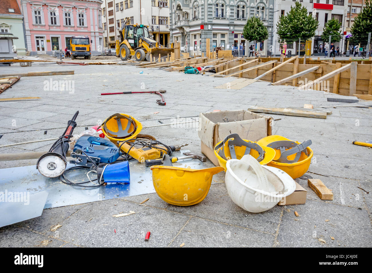 Hardhat and power tool are on the ground with plastic kettle for coffee or tea. - Stock Image