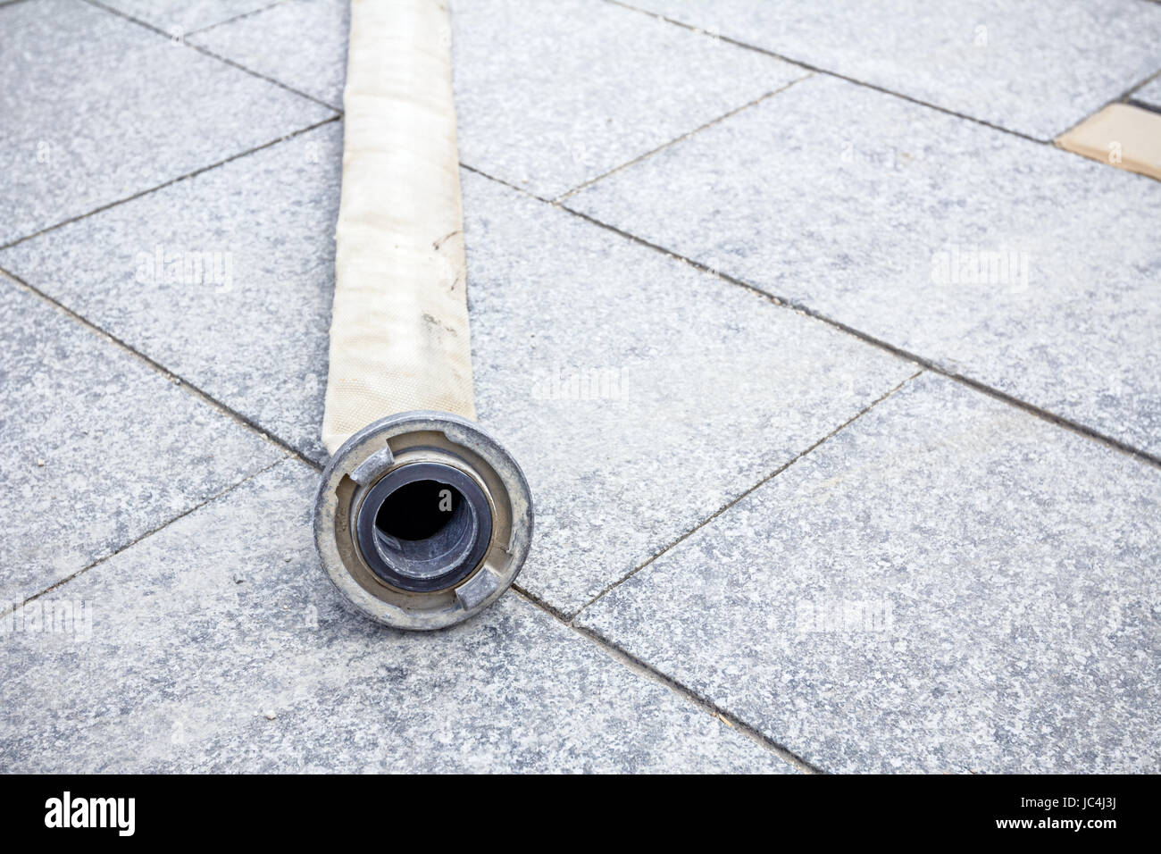 Front view on clutch of fire hose on tiled background. - Stock Image