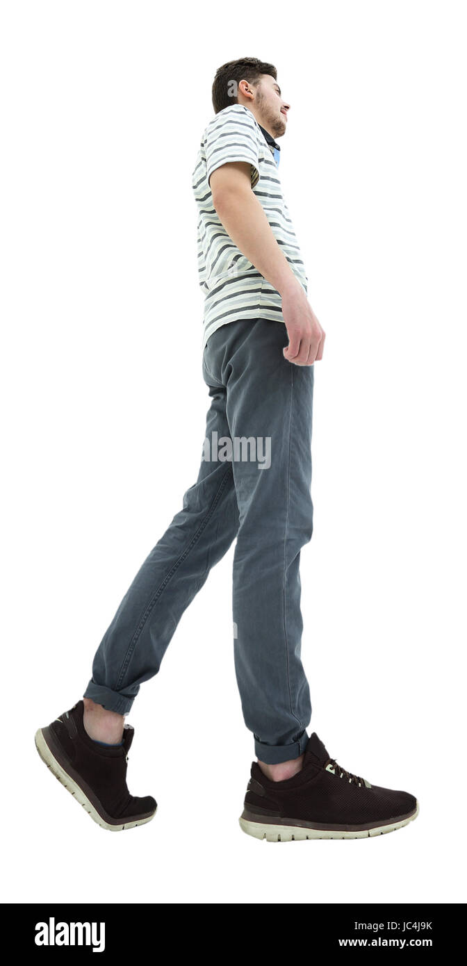 Side view of a smiling young casual man walking , On white backg - Stock Image