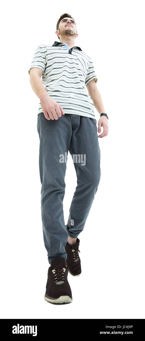 Bottom view of a smiling young casual man walking, on a white ba Stock Photo
