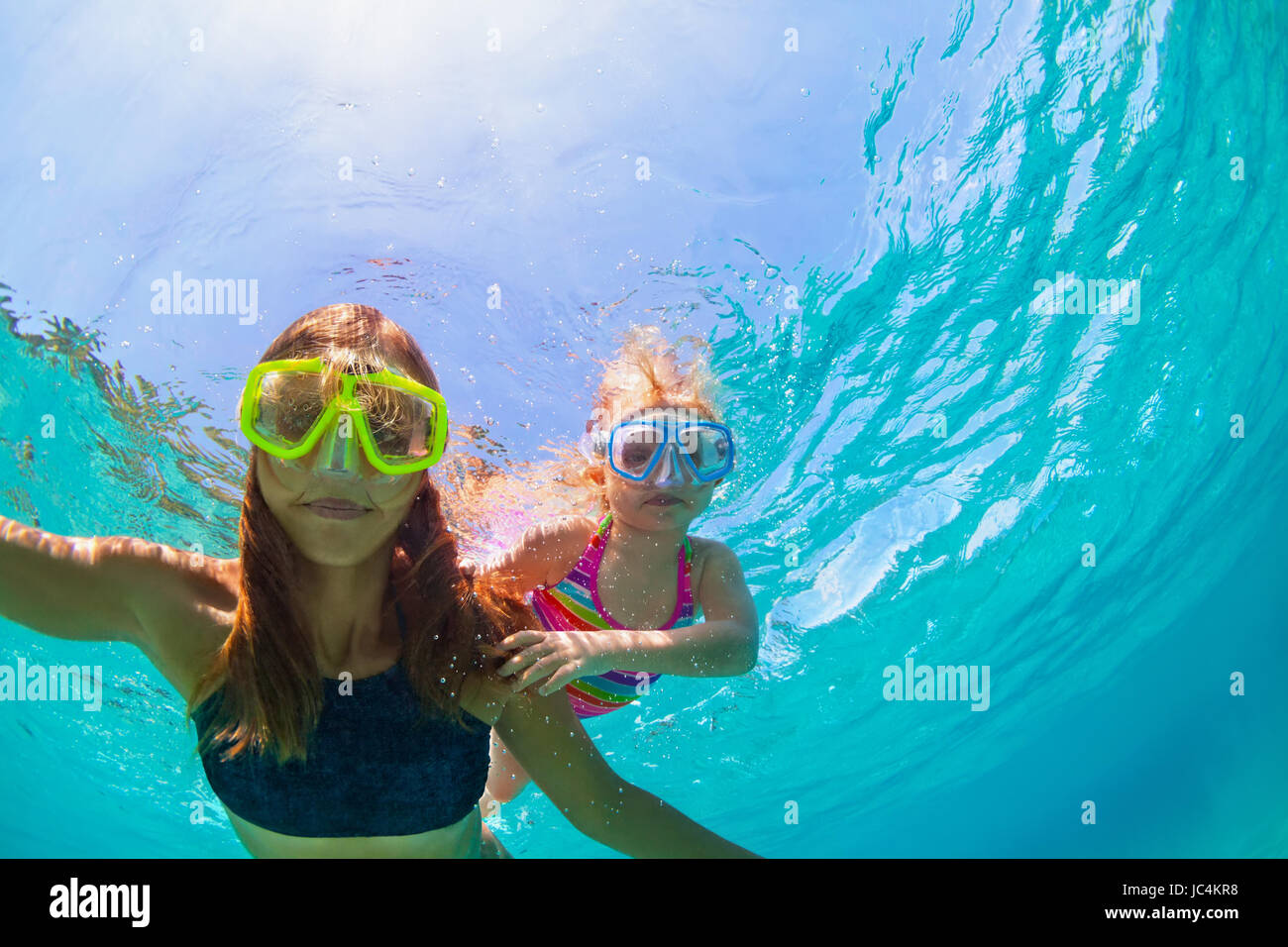 Happy family - mother with baby girl dive underwater with fun in sea pool. Healthy lifestyle, active parent, people - Stock Image