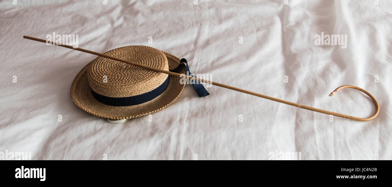 School cane and boater on bed - Stock Image