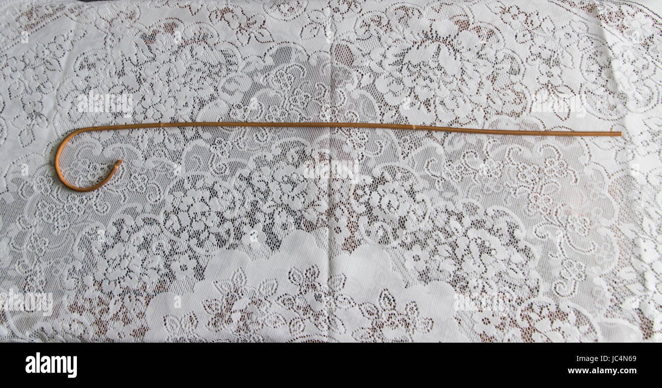 School cane on lace tablecloth - Stock Image