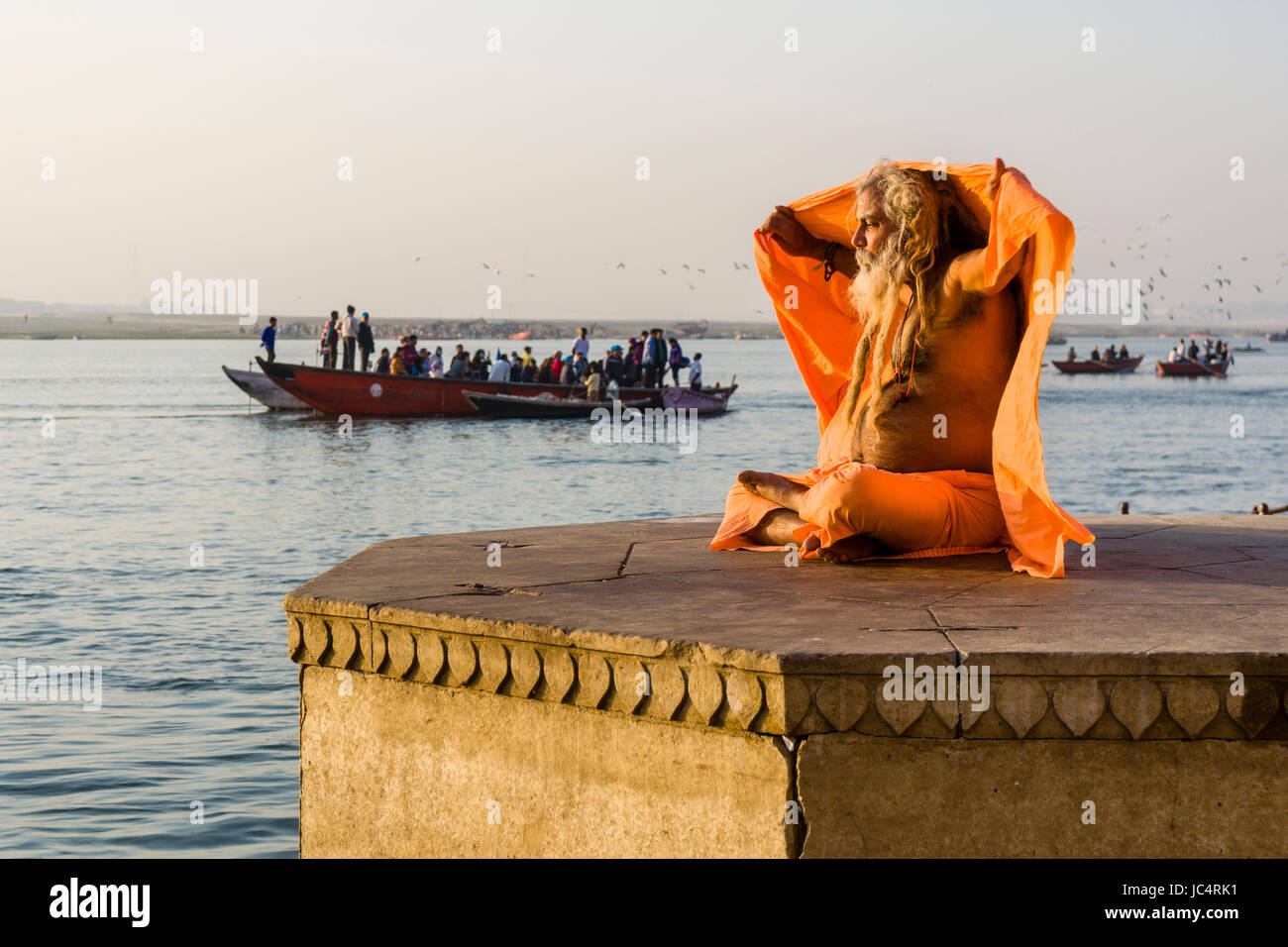 A Sadhu, holy man, is sitting on a platform at the holy river Ganges at Dashashwamedh Ghat, Main Ghat, in the suburb - Stock Image