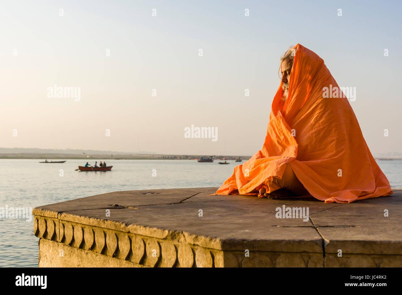 A Sadhu, holy man, is sitting and meditating on a platform at the holy river Ganges at Dashashwamedh Ghat, Main - Stock Image