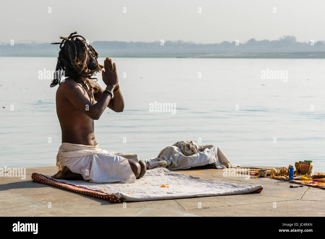 A Sadhu, holy man, is sitting and praying on a platform at the holy river Ganges at Meer Ghat in the suburb Godowlia - Stock Image
