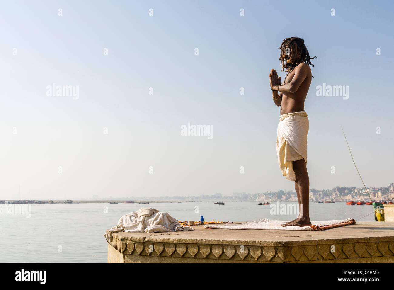 A Sadhu, holy man, is standing and praying on a platform at the holy river Ganges at Meer Ghat in the suburb Godowlia - Stock Image