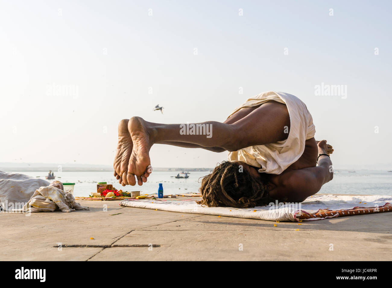 A Sadhu, holy man, is practising yoga asana on a platform at the holy river Ganges at Meer Ghat in the suburb Godowlia - Stock Image