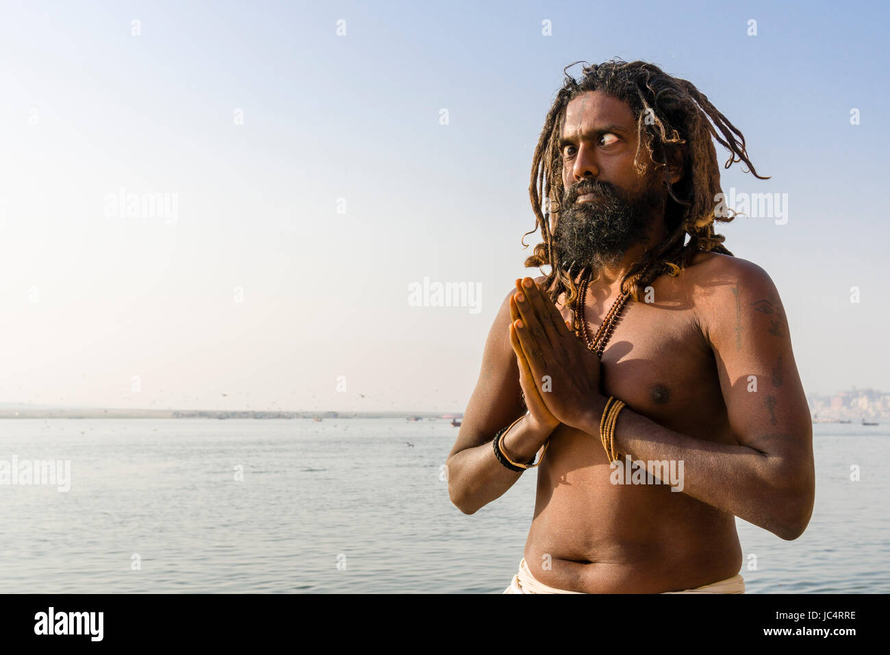 A Sadhu, holy man, is practising eye yoga asana on a platform at the holy river Ganges at Meer Ghat in the suburb - Stock Image