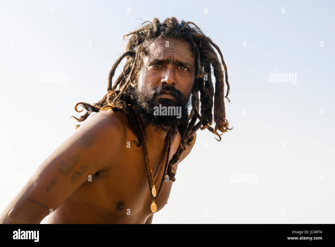 Portrait of a Sadhu, holy man, on a platform at the holy river Ganges at Meer Ghat in the suburb Godowlia - Stock Image