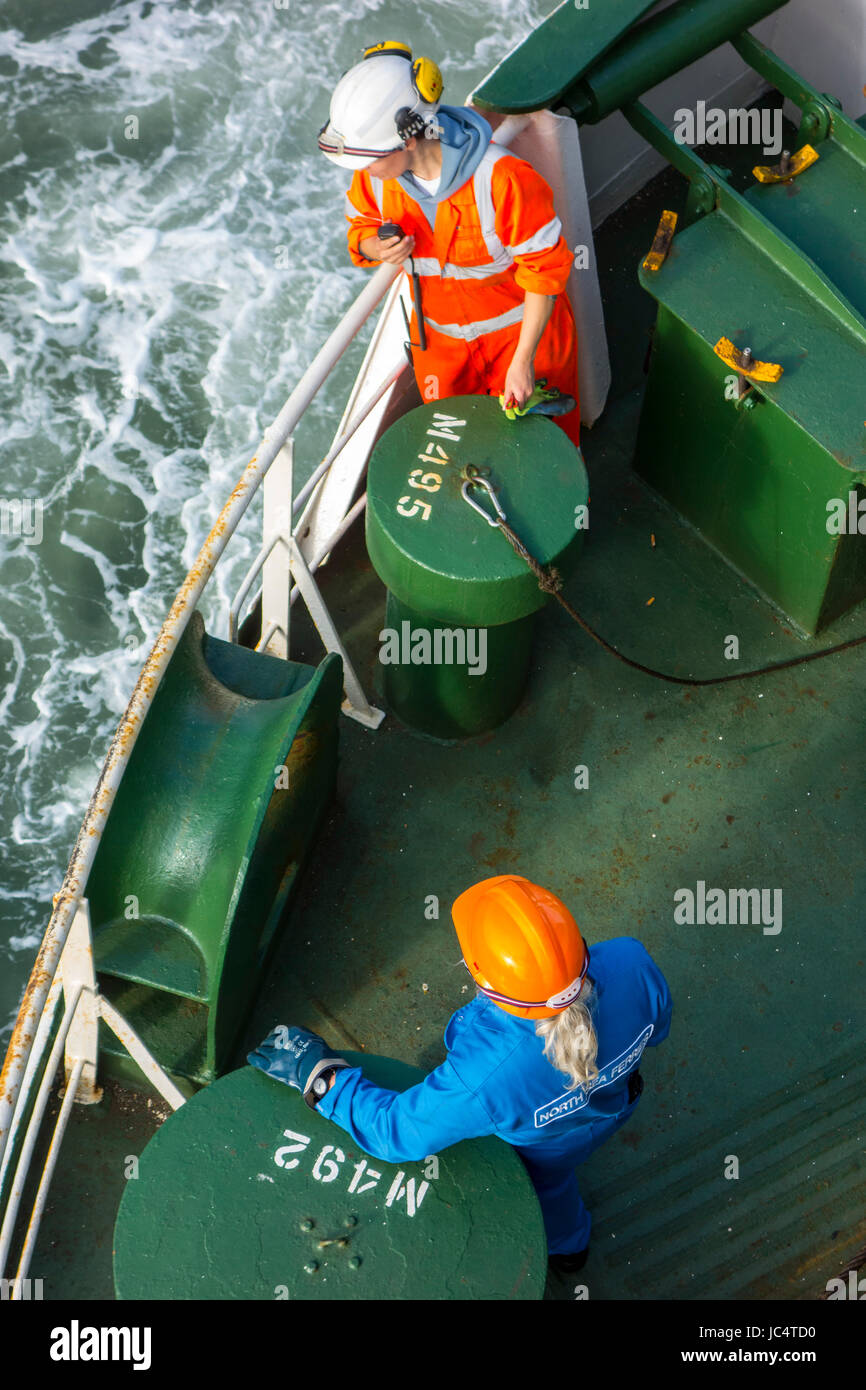 Male and female crew member in orange and blue overalls and wearing safety helmets working on deck of ferry boat - Stock Image