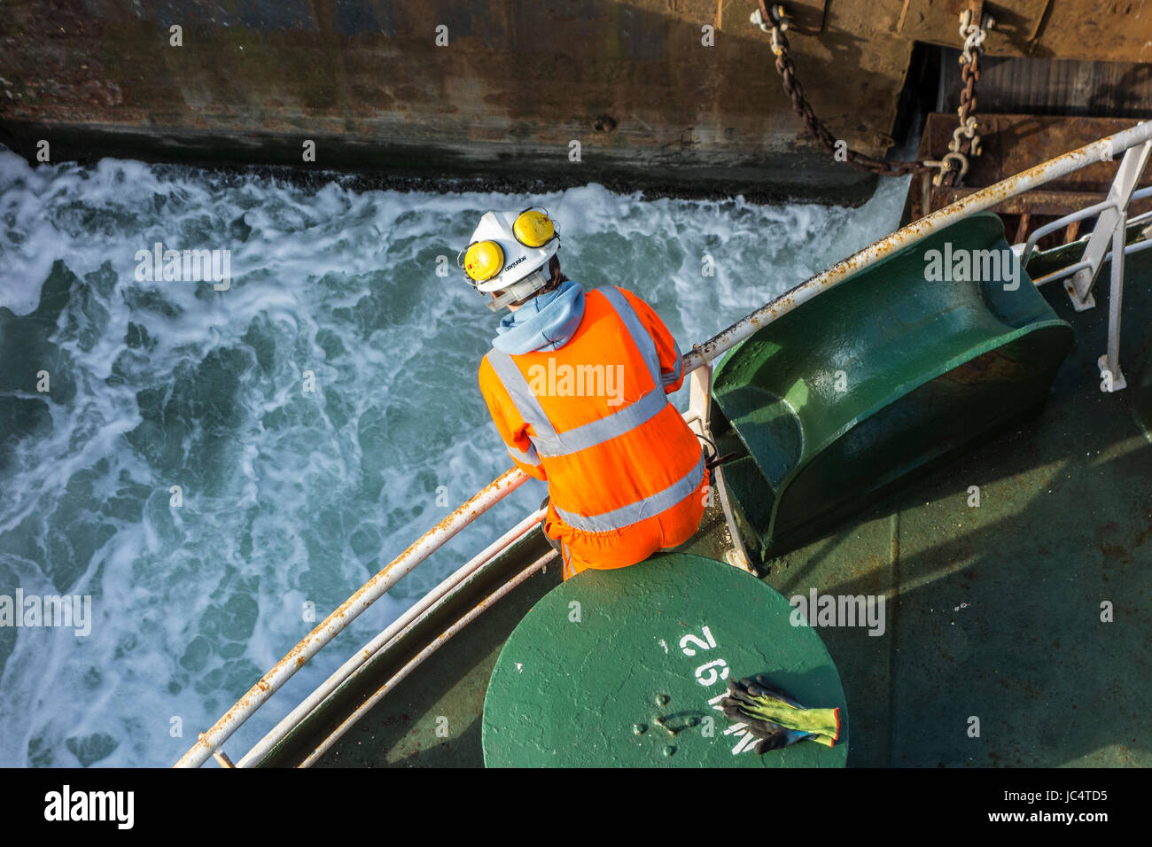 Female crew member in orange overall and wearing safety helmet working on deck of car carrier / cargo ship in seaport Stock Photo