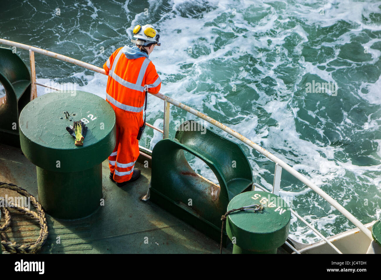 Female crew member in orange overall and wearing safety helmet working on deck of car carrier / cargo ship at sea Stock Photo