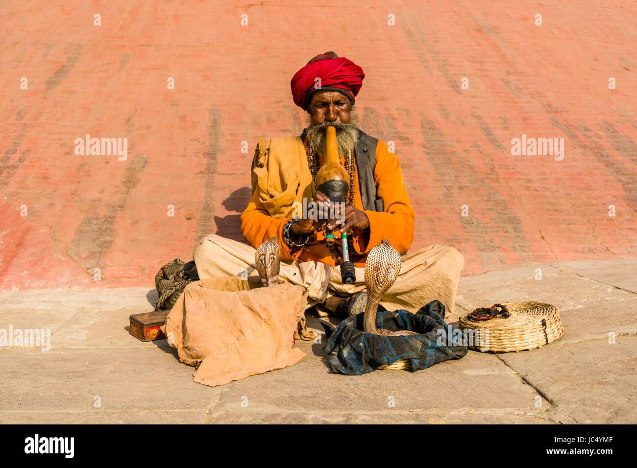 A snake charmer is playing flute to get his cobra dancing at the holy river Ganges at Dashashwamedh Ghat, Main Ghat, in the suburb Godowlia Stock Photo