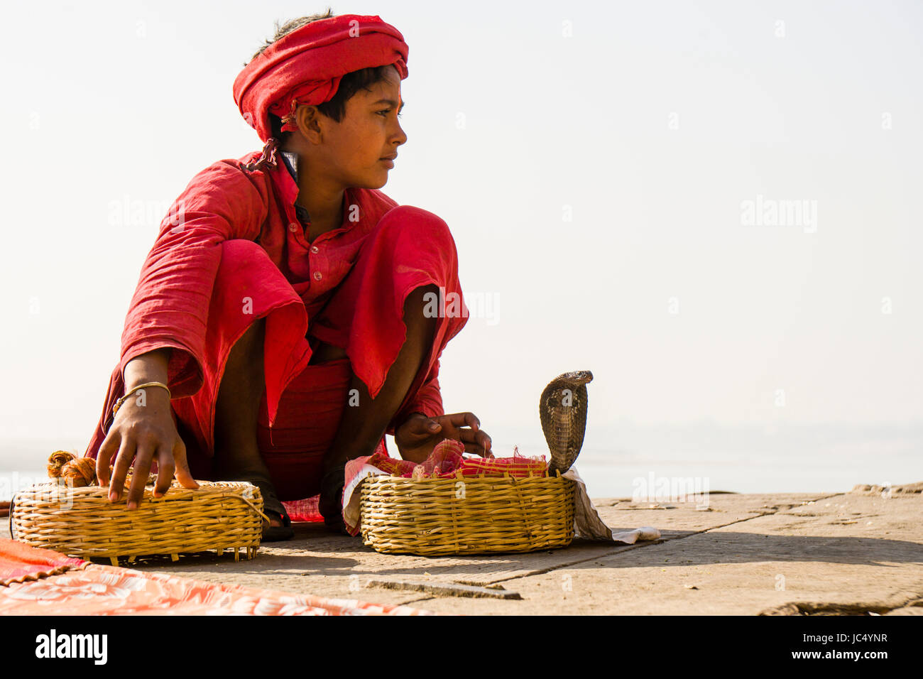 A snake charmer is sitting with his cobras in a basket at the holy river Ganges at Dashashwamedh Ghat, Main Ghat, in the suburb Godowlia Stock Photo