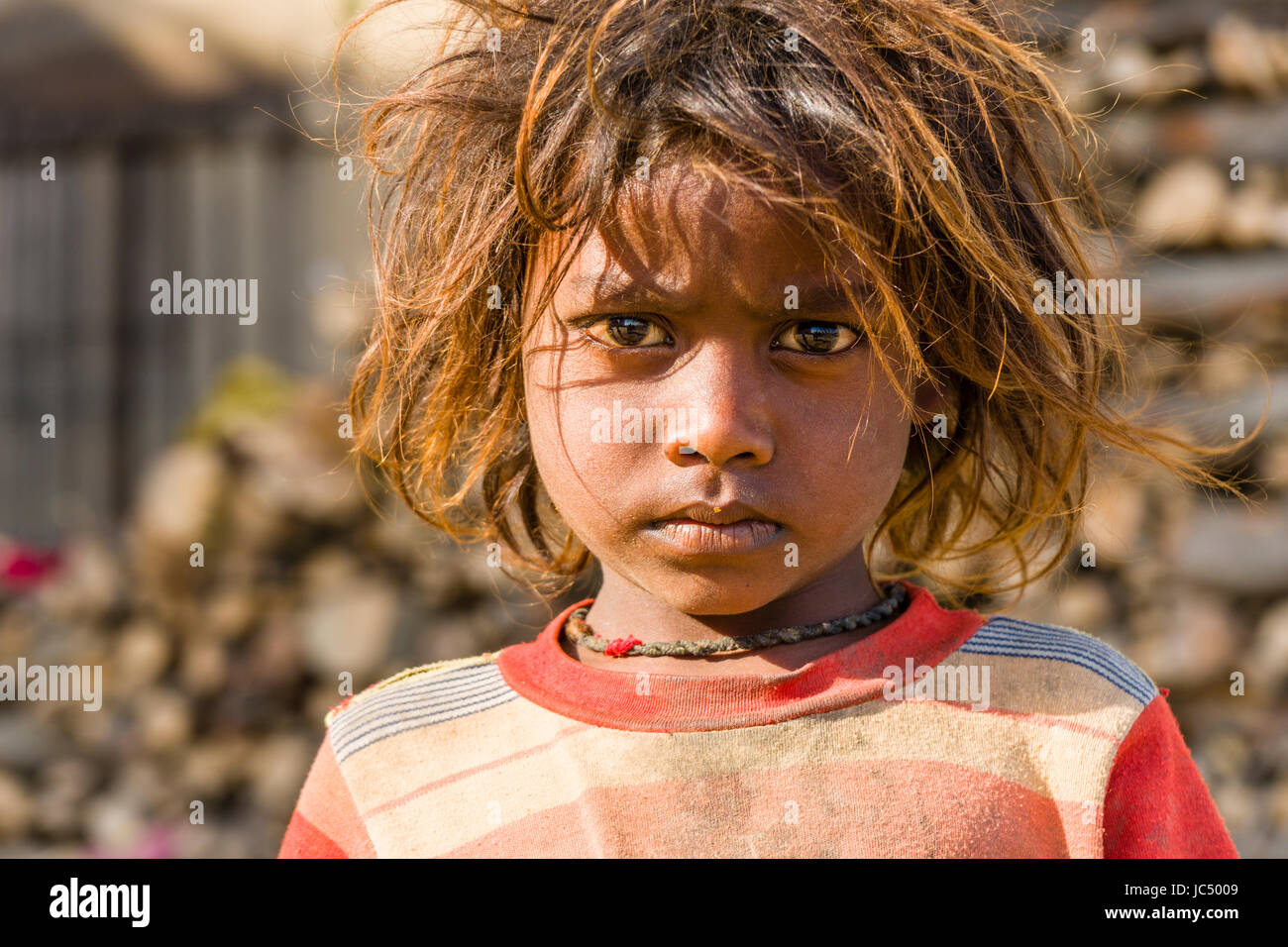 Portrait of a child, begging, at the holy river Ganges at Lalita Ghat in the suburb Godowlia - Stock Image