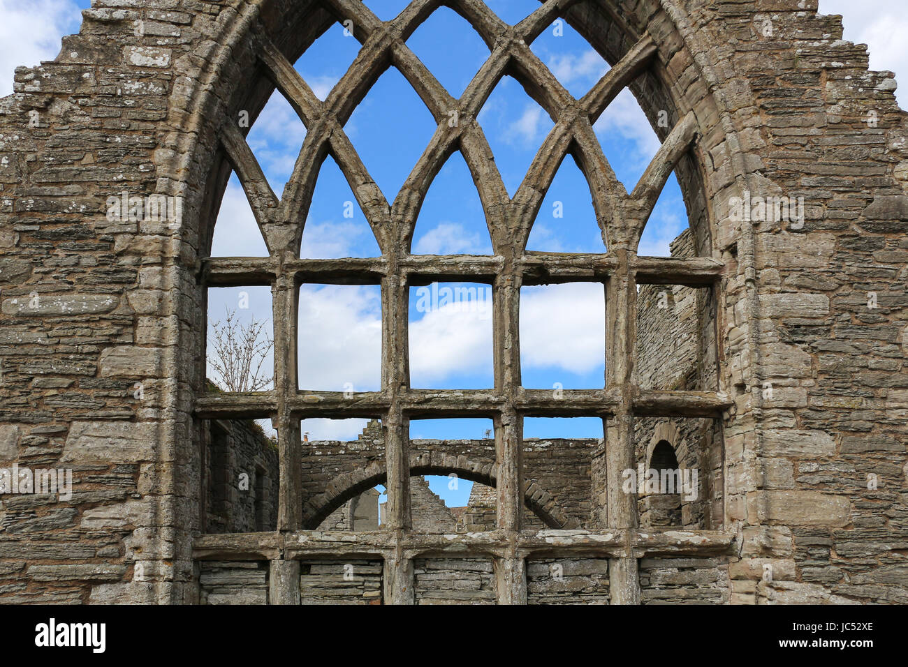 The five lighted south traceried window of Old St. Peter's Kirk ruin in Thurso, Scotland. The 12th Century church - Stock Image