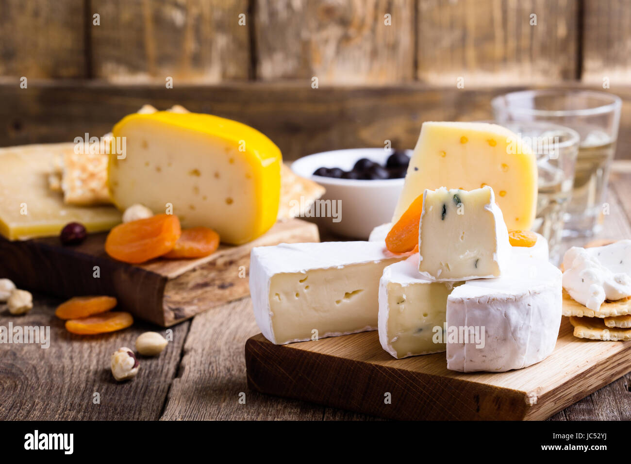 Cheese and wine party  table, perfect holiday appetizer on rustic wooden board - Stock Image