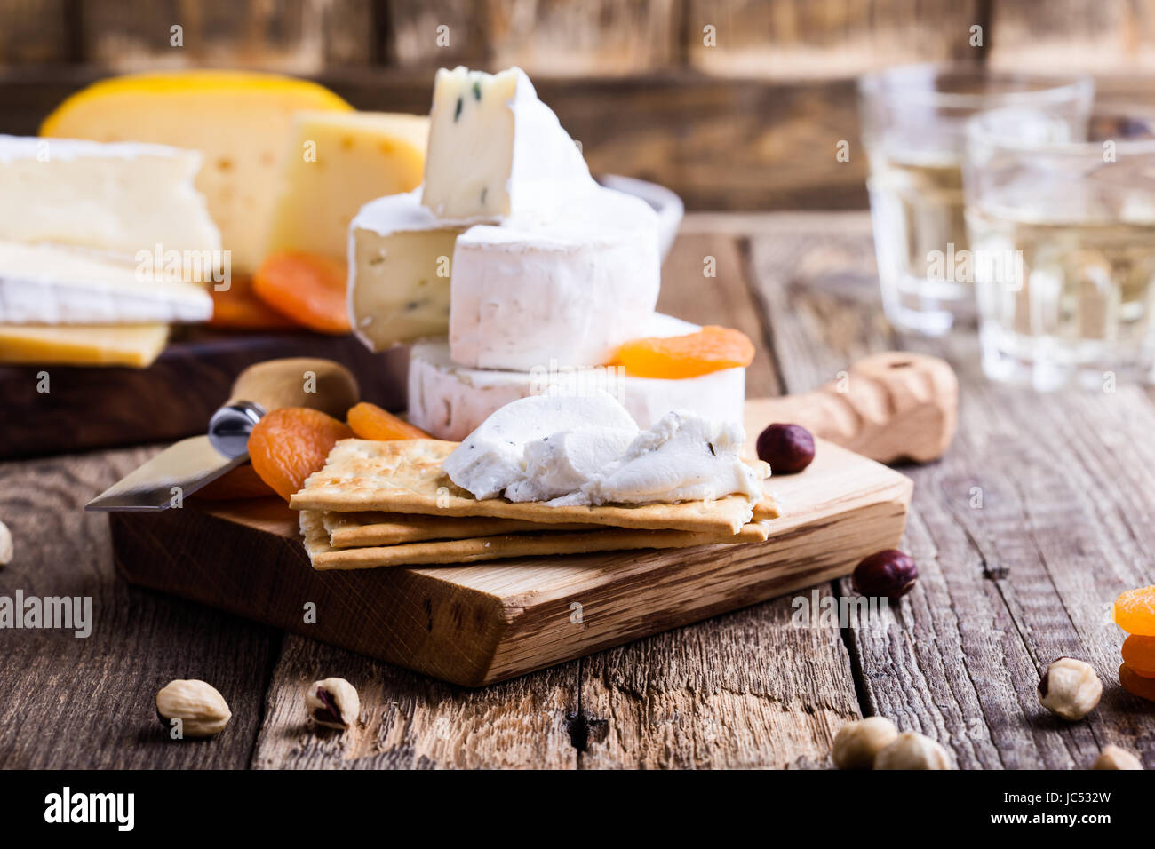 Cheese and wine party  table, perfect holiday appetizer on rustic wooden board, goat cheese with  crackers - Stock Image