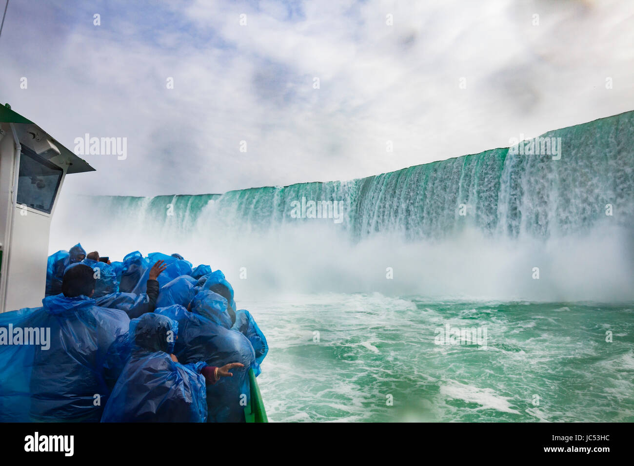 "A boat of tourists huddle under blue plastic ponchos to keep the drenching waterfall spray off as the boat, ""Maid - Stock Image"