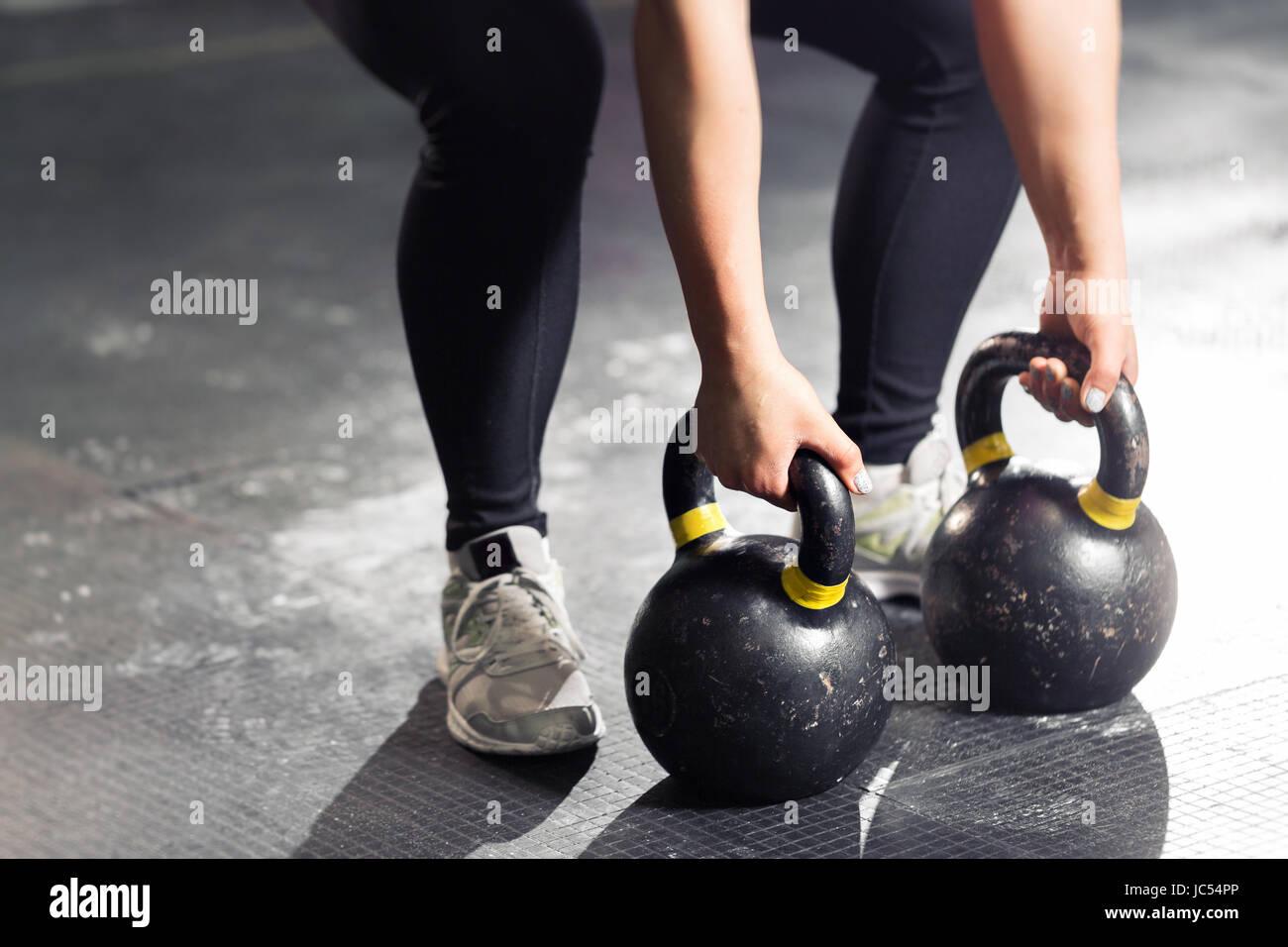 Kettlebell on floor. Girl training in gym - Stock Image