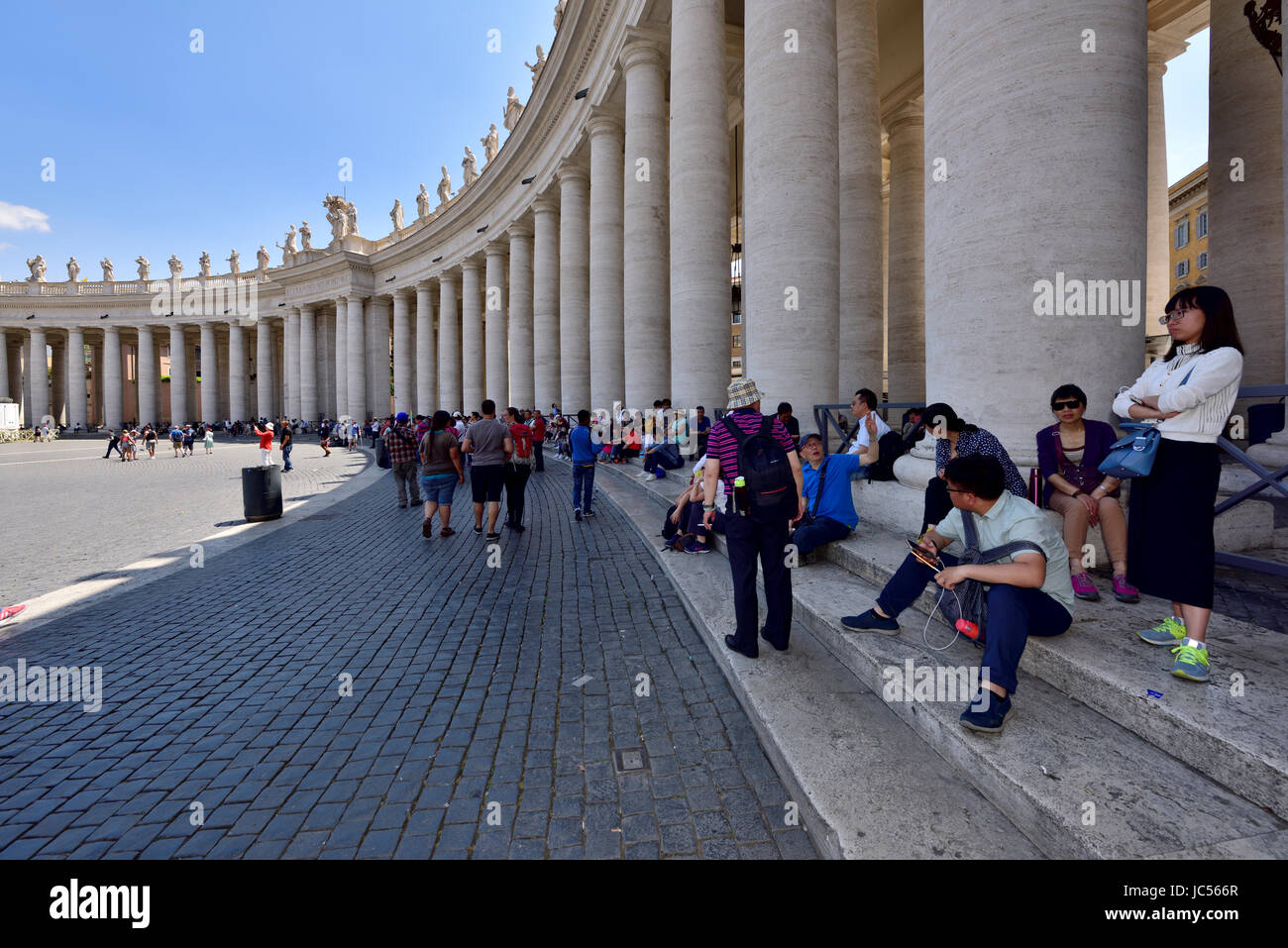 Saint Peter's Square, Vatican City, Rome. People staying cool in shade - Stock Image