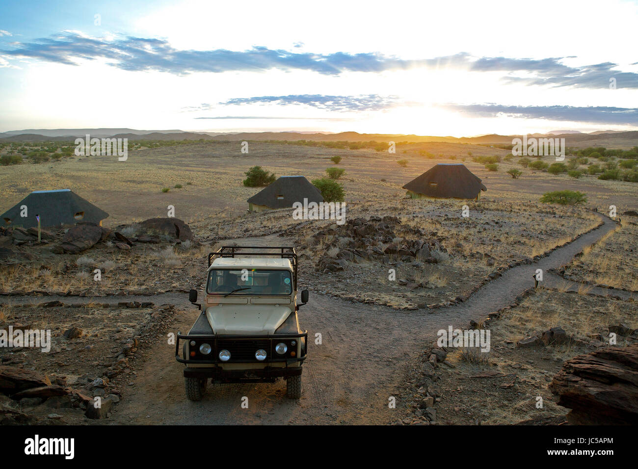 Parked car with huts in background - Stock Image