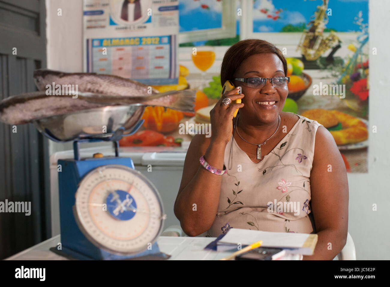 A small business owner, weighing out her fish, whilst talking on her mobile Nigeria, Africa Stock Photo