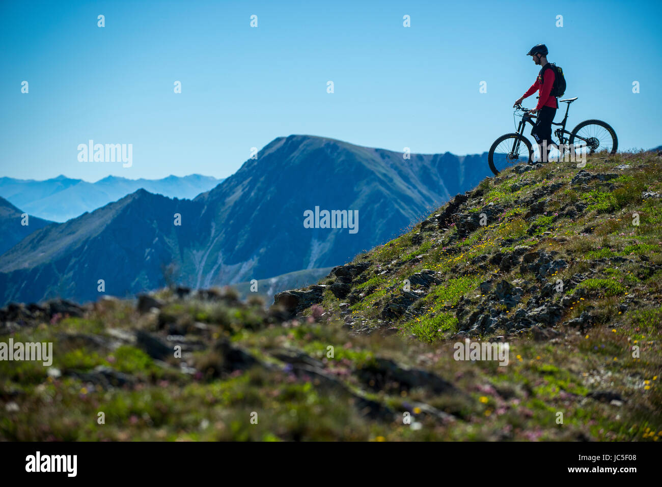A mountain biker rides along a mountain ridge in Andorra in the Pyrenees. - Stock Image