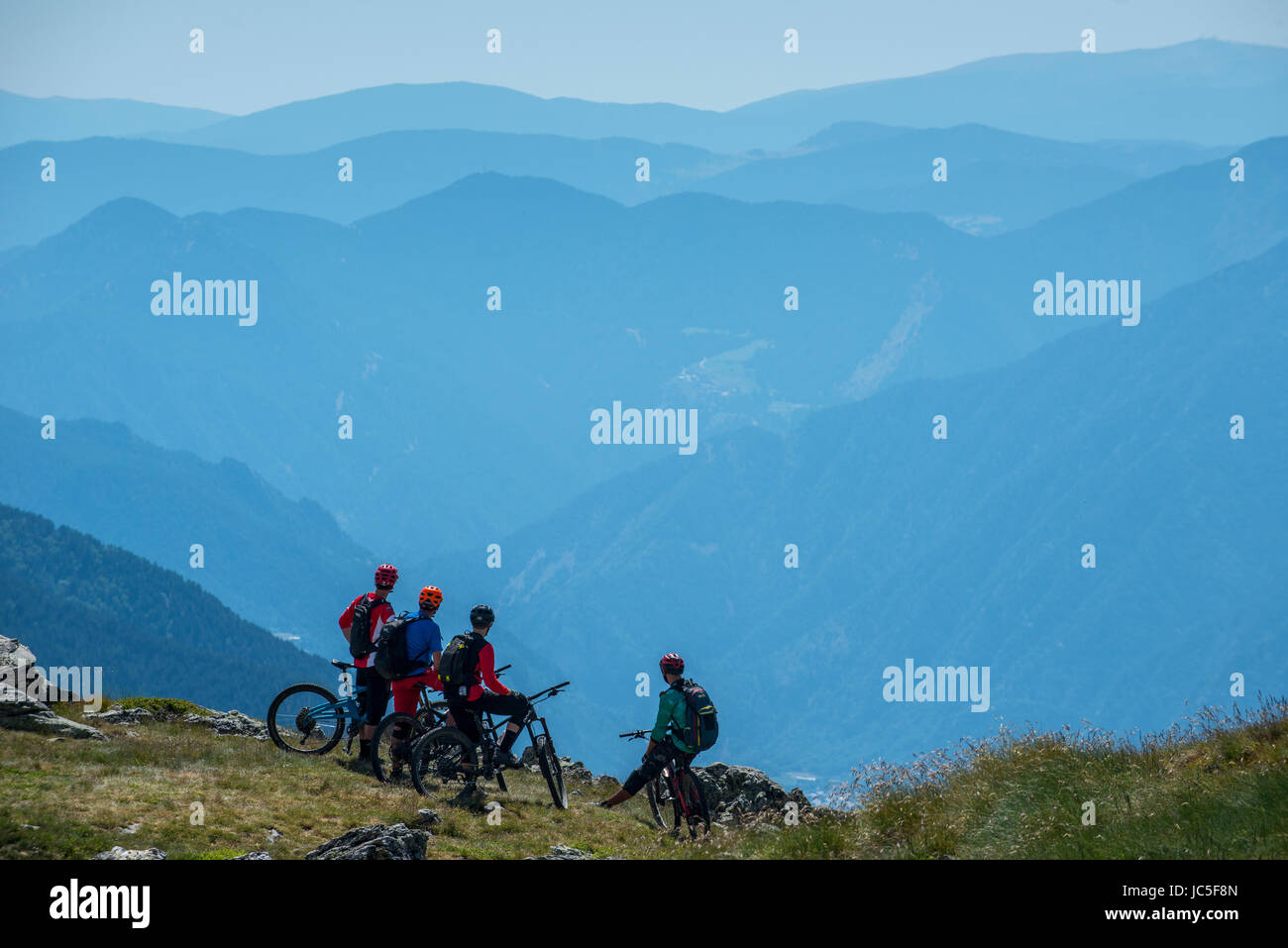 A group of mountain bikers ride a trail high in the Pyrenees, Andorra. - Stock Image